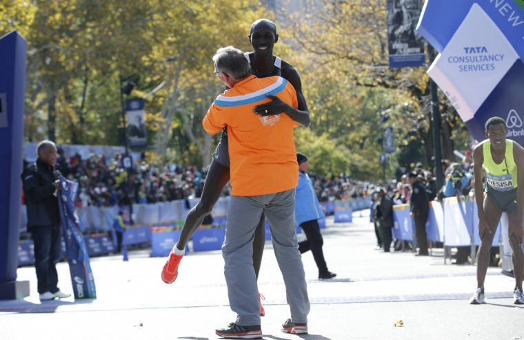 A supporter lifts Wilson Kipsang of Kenya off the ground after he crossed the finish line to win the men's professional division of the 2014 New York City Marathon in Central Park in Manhattan. At right is second place finisher Lelisa Desisa of Etheopia.(Mike Segar/Reuters)