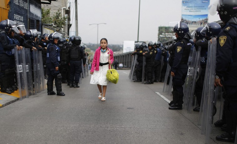A girl walks past riot policemen guarding one of the access roads to Benito Juarez International airport after demonstrators staged a protest over the 43 missing Ayotzinapa students in Mexico City November 20, 2014. Forty-three missing students abducted by corrupt police in southwest Mexico weeks ago were apparently incinerated by drug gang henchmen and their remains tipped in a garbage dump and a river, the Mexican government said. (Tomas Bravo/Reuters)