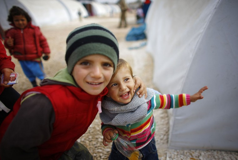 Kurdish refugee children, who are from the Syrian town of Kobani, smile as they play in a refugee camp in the border town of Suruc, Sanliurfa province November 20, 2014. (Osman Orsal/Reuters)