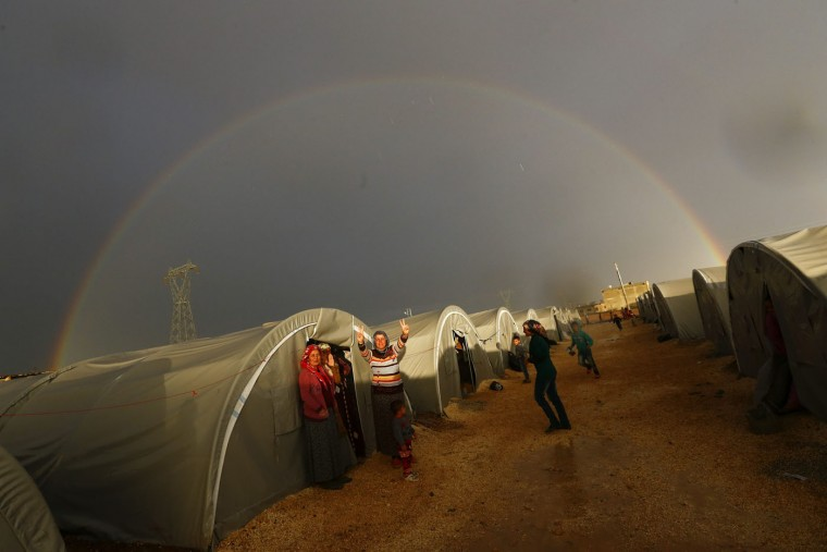 "A Kurdish refugee from the Syrian town of Kobani shows victory sign as a rainbow forms over the camp in the southeastern town of Suruc, Sanliurfa province, in this October 16, 2014 file photo. Reuters photographers have chronicled Kurdish refugee crises over the years. In 1991 Srdjan Zivulovic documented refugees in Cukurca who had escaped a military operation by Saddam Hussein's government in Iraq aimed at ""Arabising"" Kurdish areas in the north. Hundreds of thousands fled into Turkey and Iran. Images shot in recent months show familiar scenes as crowds of people flee Islamic State militants in Syria. There are as many as 30 million Kurds, spread through Turkey, Iraq, Syria and Iran. Most Kurds are Sunni Muslims, but tend to feel more loyalty to their Kurdishness, rather than their religion. (Kai Pfaffenbach/Files/Reuters)"