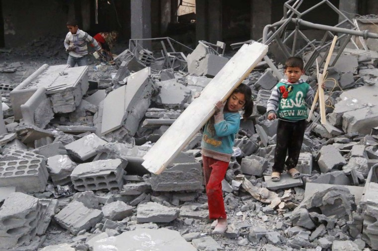 Children collect items from among the debris of a school for the deaf and mute, destroyed in what activists said were overnight U.S.-led air strikes against the Islamic State, in Raqqa November 24, 2014. Raqqa, in eastern Syria, is controlled by the Islamic State. The United States and its allies have conducted two dozen strikes against Islamic State militants since Friday, launching nine strikes in Syria and 15 strikes in Iraq, according to U.S. Central Command. (Nour Fourat/Reuters)