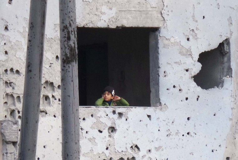 A boy looks out from a window inside the bullet-riddled facade of his home after what activists said were overnight U.S.-led air strikes against the Islamic State, in Raqqa November 24, 2014. Raqqa, in eastern Syria, is controlled by the Islamic State. The United States and its allies have conducted two dozen strikes against Islamic State militants since Friday, launching nine strikes in Syria and 15 strikes in Iraq, according to U.S. Central Command. (Nour Fourat/Reuters)