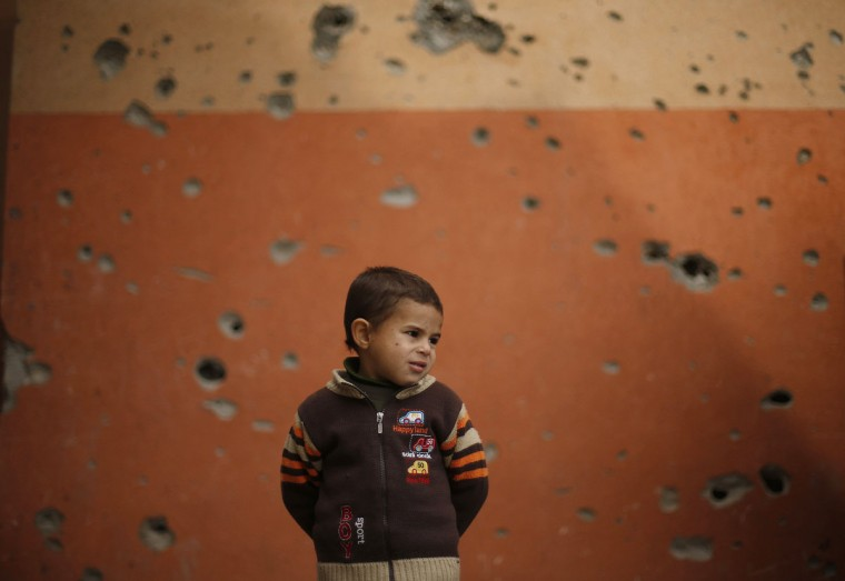 A Palestinian boy stands outside a mosque, that witnesses said was damaged by Israeli shelling during the most recent conflict between Israel and Hamas, on a winter day in Beit Hanoun town, northern Gaza Strip, November 25, 2014. (REUTERS/Suhaib Salem)