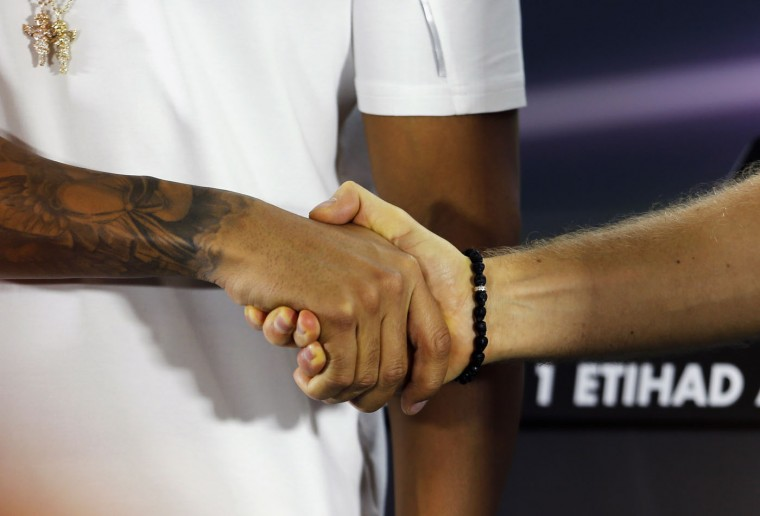 Mercedes Formula One driver Lewis Hamilton of Britain (L) shakes hands with his team mate Nico Rosberg of Germany as they arrive for a press conference at the Yas Marina circuit before the start of the Abu Dhabi Grand Prix November 20, 2014. (Hamad I Mohammed/Reuters)