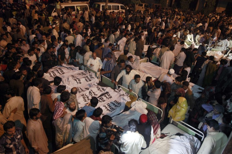 Pakistani relatives gather beside the covered bodies of victims who were killed in suicide bomb attack in Wagah border near Lahore. At least 45 people were killed on Sunday when a suicide bomber blew himself up on the Pakistani-Indian border, police said, just after a daily ceremony when troops from both sides simultaneously lower the two nations' flags. (Mohsin Raza/Reuters)