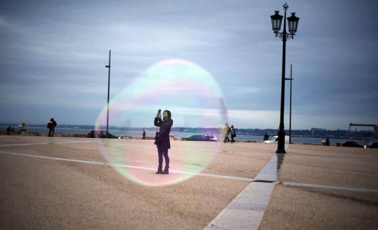 A tourist is seen through a soap bubble as she takes a picture at Comercio square in downtown Lisbon November 18, 2014. (Rafael Marchante/Reuters)