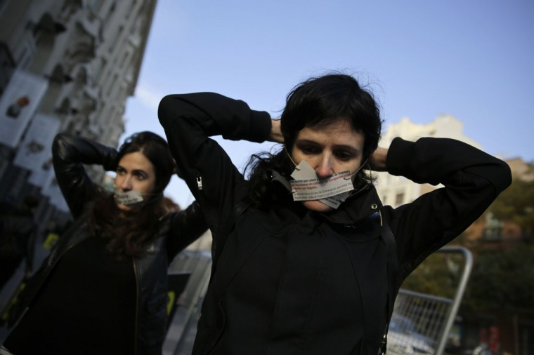 Amnesty International activists cover their mouths during a protest against the government's new security law, near the Spanish parliament in Madrid, November 25, 2014. (REUTERS/Andrea Comas)