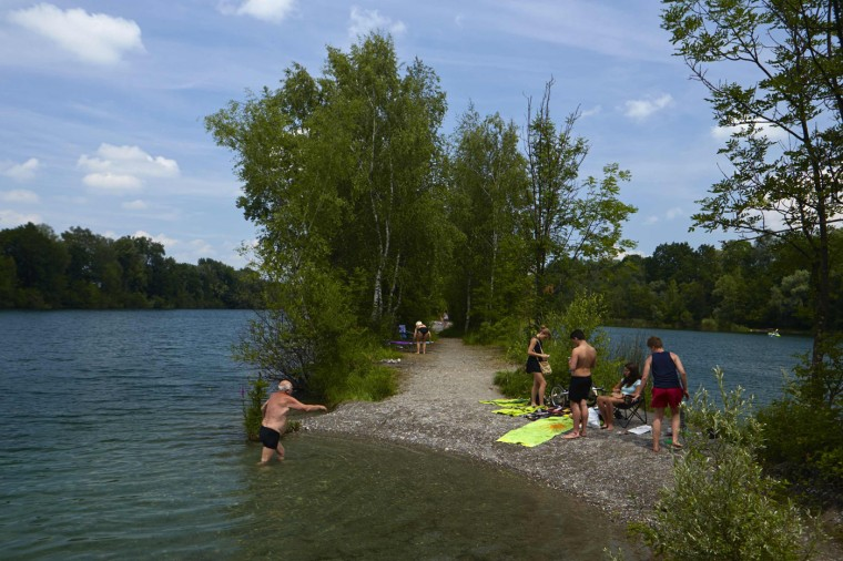 People relax near the water in the Alter Rhein at the border between Austria (R) and Switzerland in Diepoldsau May 14, 2014.
