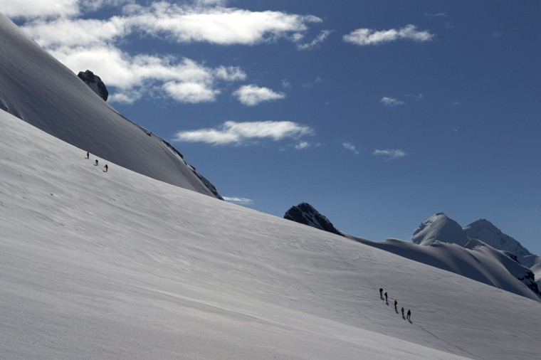 Roped parties of climbers walk on a glacier marking the border with Switzerland (left) and Italy on the way to the summit of the Breithorn at 4,164 metres (13,661 feet) in the Alpine resort of Zermatt August 4, 2014.