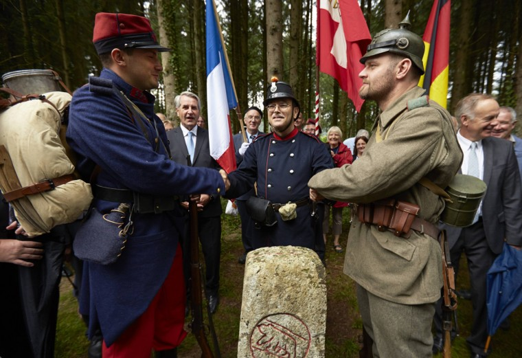 Military enthusiasts dressed as World War I soldiers (L-R French, Swiss and German) shake hands above a marker during a re-enactment in Le Largin near Bonfol in the Jura July 20, 2014.