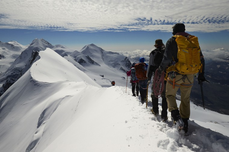 Roped up climbers leave the summit of Breithorn at 4,164 metres (13,661 feet) on the ridge marking the border with Switzerland (left) and Italy in the Alpine resort of Zermatt August 4, 2014.