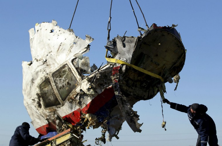 Local workers transport a piece of the Malaysia Airlines flight MH17 wreckage at the site of the plane crash near the village of Hrabove (Grabovo) in Donetsk region, eastern Ukraine November 20, 2014. (Antonio Bronic/Reuters)
