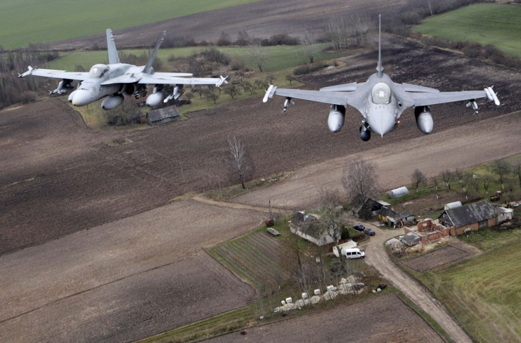 Portuguese Air Force fighter F-16 (R) and Canadian Air Force fighter CF-18 Hornet patrol over Baltics air space, from the Zokniai air base near Siauliai November 20, 2014. NATO pilots practised scrambling their jets on Wednesday, in preparation for potential further unauthorised Russian jets encountered on Baltic patrols. The flight drills were part of the NATO Baltic Air Policing Mission, a collective defence project which has been running for a decade. (Ints Kalnins/Reuters)