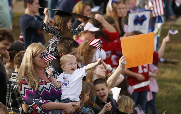 A young boy waves small U.S. flags as an airplane bringing paratroopers with the 1st Brigade Combat Team, 82nd Airborne Division home from Afghanistan, arrives at Pope Army Airfield in Fort Bragg, North Carolina November 5, 2014. Approximately 300 troops arrived home after being deployed since February 2014, according to the military. (Chris Keane/Reuters)
