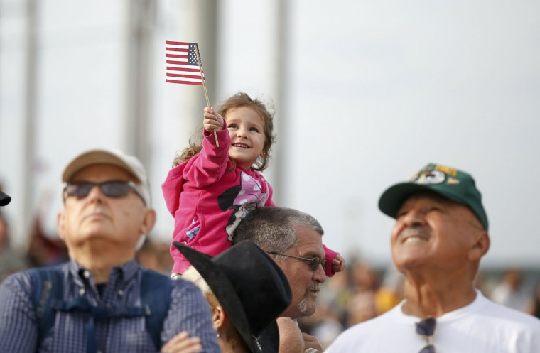A young girl waves a flag as she and others watch the airplane flying paratroopers with the 1st Brigade Combat Team, 82nd Airborne Division as they return home from Afghanistan, at Pope Army Airfield in Fort Bragg, North Carolina November 5, 2014. Approximately 300 troops arrived home after being deployed since February 2014, according to the military. (Chris Keane/Reuters)