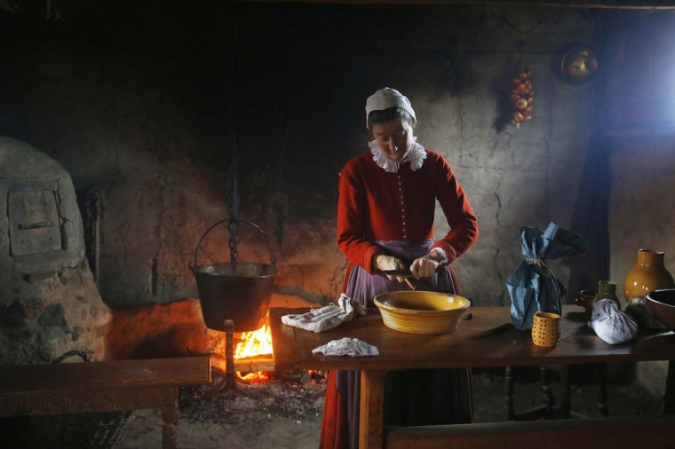 A woman playing the role of Bridget Fuller scrapes cinnamon into a bowl to make pancakes in a home at Plimoth Plantation in Plymouth, Massachusetts November 24, 2014. Plimouth Plantation is a living museum portraying the life of the Native Americans and the English colonists in 1627, seven years after the colonists' arrival. The three-day harvest festival and feast at the Plimoth Colony in 1621 is the model for the modern-day Thanksgiving holiday in the United States, according to the museum. (Brian Snyder/Reuters)