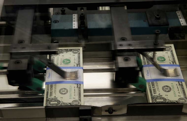 United States one dollar bills are put in packaging bands during production at the Bureau of Engraving and Printing in Washington November 14, 2014. (Gary Cameron/Reuters)