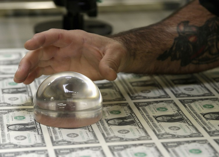 A technician inspects United States one dollar bills during production at the Bureau of Engraving and Printing in Washington November 14, 2014. (Gary Cameron/Reuters)