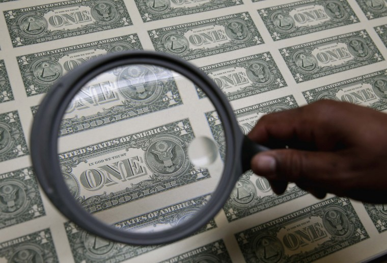United States one dollar bills are inspected under a magnifying glass during production at the Bureau of Engraving and Printing in Washington November 14, 2014. (Gary Cameron/Reuters)