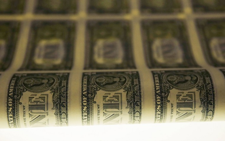 A sheet of United States one dollar bills is seen on a light table during production at the Bureau of Engraving and Printing in Washington November 14, 2014. (Gary Cameron/Reuters)