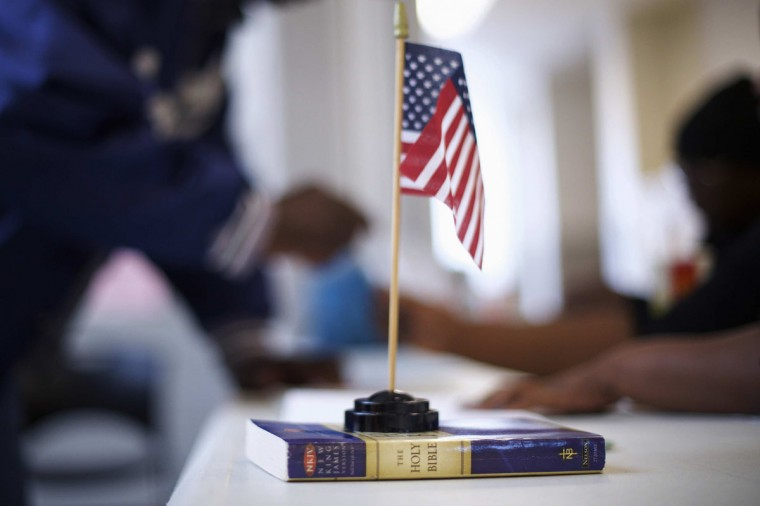 A miniature U.S. flag rests on a copy of the Bible at voter registration at West Philadelphia High School on U.S. midterm election day morning in Philadelphia, Pennsylvania, November 4, 2014. (Mark Makela/Reuters)