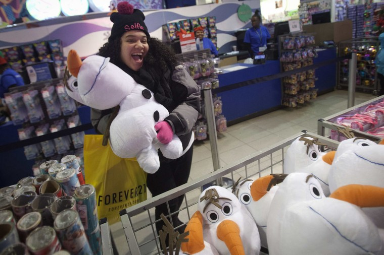 A girl poses with an Olaf plush toy from Disney's Frozen toy line at the Toys R Us store in Times Square in New York November 27, 2014. Toys R Us opened on Thanksgiving evening at 5pm, ahead of many other Black Friday retailers. (Carlo Allegri/Reuters)