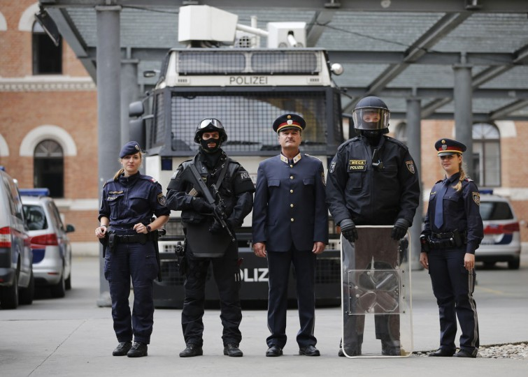 """Austrian police officers in front of a water cannon at their headquarters in Vienna October 8, 2014. The uniforms include (L to R) light demonstration uniform, full combat adjustment for life threatening mission including gun (not used for riots in Austria), normal daily life uniform of commander, uniform of riot police officer, and normal uniform of police officer. In Austria, the use of lethal force is permitted to tackle rioting or to detain a dangerous suspect, but only when less dangerous methods """"appear inappropriate or have proved to be ineffective"""", and with the aim of avoiding serious injury where possible. The use must be proportionate, and be preceded by a warning. Picture taken October 8. (Leonhard Foeger/Reuters)"""
