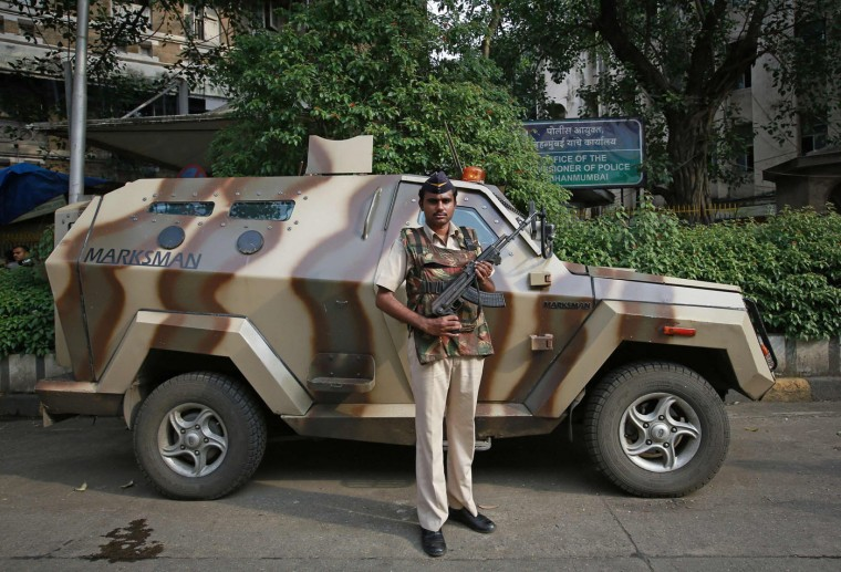 A Mumbai police constable as he stands guard next to an armoured vehicle outside the police commissioner's office in Mumbai October 1, 2014. In India, the Rapid Action Force (RAF) are called on for violent disorder that the police are unable to contain. They require an on-the-spot magistrate's consent and must issue a warning before each escalation of the use of force, from verbal warning to water cannon and tear gas, then to rubber bullets or baton rounds, and then to firearms. Picture taken October 1. (Danish Siddiqui/Reuters)