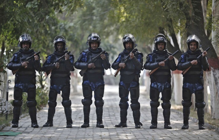 India's Rapid Action Force (RAF) personnel pose for pictures inside their base camp in New Delhi. In India, the RAF are called on for violent disorder that the police are unable to contain. They require an on-the-spot magistrate's consent and must issue a warning before each escalation of the use of force, from verbal warning to water cannon and tear gas, then to rubber bullets or baton rounds, and then to firearms. Picture taken November 6. (Adnan Abidi/Reuters)