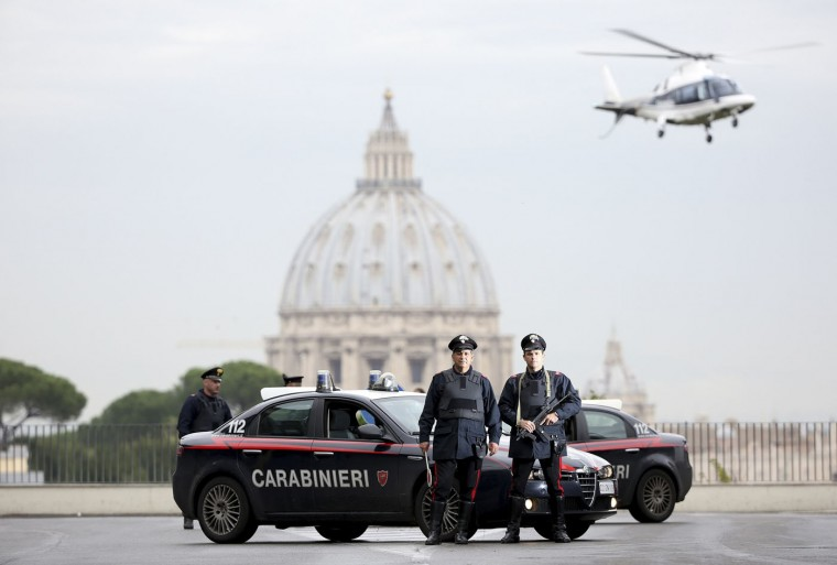 """Italian Carabinieri in front of St. Peter's Basilica as a Carabinieri helicopter flies overhead, in Rome. In Italy, police and the paramilitary Carabinieri follow the same guidelines, which say that the use of weapons is allowed only in the line of duty, when it is an """"unavoidable necessity to overcome resistance, stop violence, or prevent a [serious] crime"""", and that the response must be proportionate to the situation. Picture taken November 12. (Alessandro Bianchi/Reuters)"""