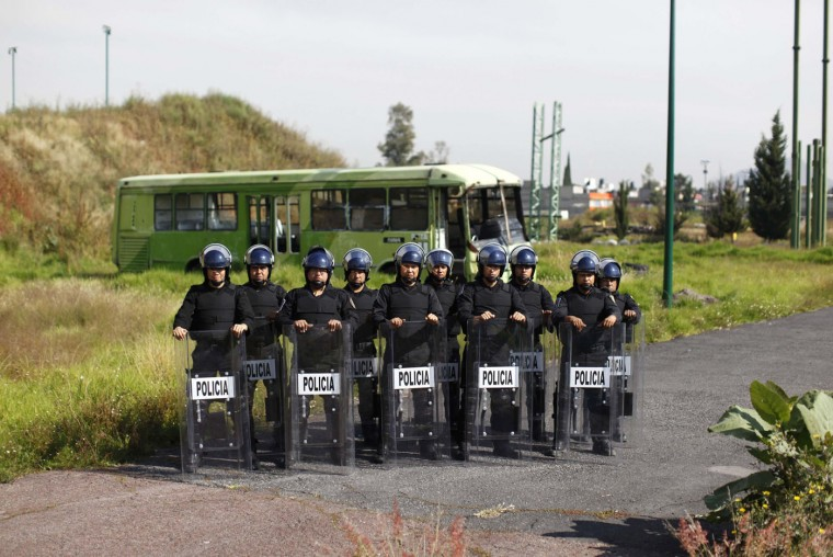 """Members of the Task Force for Mexico City in front of a bus used for training, at their base in Mexico City October 15, 2014. In Mexico, """"when violent action by a crowd cannot be deterred, a scale of force will be applied progressively consisting of 1. verbal persuasion or deterrence 2. reduced physical movements 3. use of non-lethal incapacitating weapons, and 4. use of firearms or lethal force"""". Picture taken October 15. (Claudia Daut/Reuters)"""