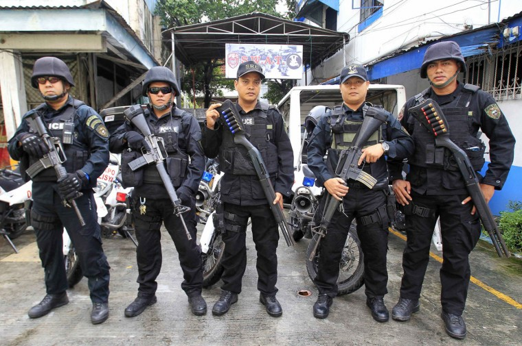 Members of the Philippine National Police Special Weapons and Tactics (SWAT) team pose for a picture outside a police station in Manila. In the Philippines, the use of extreme force against a suspect is allowed only if the police officer's life or that of the victim (of the suspect) is in imminent danger. Picture taken September 15. (Romeo Ranoco/Reuters)