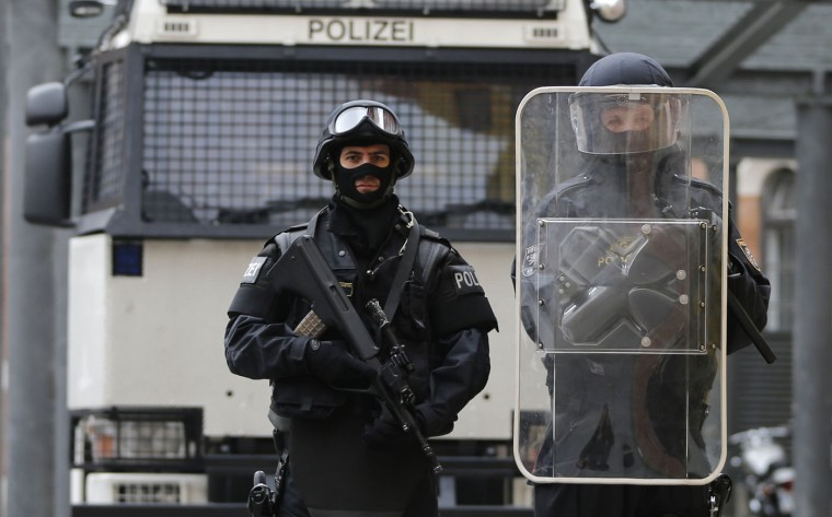 """Austrian police officers in full combat adjustment for life threatening mission including gun (not used for riots in Austria) (L) and uniform of riot police officer (R) pose in front of a water cannon at their headquarters in Vienna. In Austria, the use of lethal force is permitted to tackle rioting or to detain a dangerous suspect, but only when less dangerous methods """"appear inappropriate or have proved to be ineffective"""", and with the aim of avoiding serious injury where possible. The use must be proportionate, and be preceded by a warning. Picture taken October 8. (Leonhard Foeger/Reuters)"""