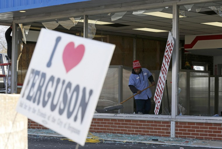 People clean up a business that was damaged in riots the previous night in Ferguson, Missouri November 25, 2014. The St. Louis area braced for another day of protests on Tuesday after a grand jury cleared a white police officer in the fatal August shooting of an unarmed black teenager, sparking a night of violent and racially charged rioting. (Jim Young/Reuters)