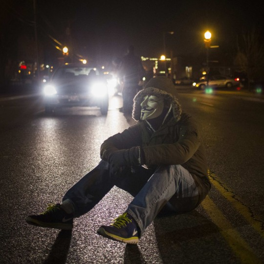 An activist, wearing a Guy Fawkes mask, blocks traffic while protesting the shooting of Michael Brown, outside the Ferguson Police Station in Missouri, November 19, 2014. Residents of Ferguson prepared on Wednesday for a grand jury report expected soon on the fatal August shooting of Brown, an event that laid bare long-simmering racial tensions in the St. Louis suburb. (Adrees Latif/Reuters)