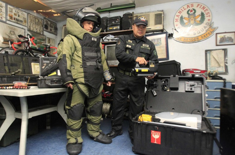 Philippine National Police bomb squad members pose for pictures with a bomb scanner and bomb suit at a police station in Manila. In the Philippines, the use of extreme force against a suspect is allowed only if the police officer's life or that of the victim (of the suspect) is in imminent danger. Picture taken September 15. (Romeo Ranoco/Reuters)