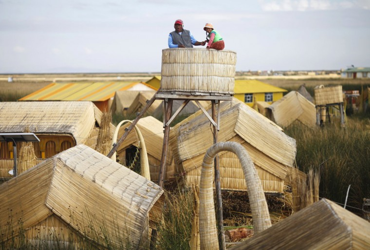 An Andean man and a child stand at the top of a tower in a Uros island at Lake Titicaca in Puno on November 5, 2014. (REUTERS/Enrique Castro-Mendivil)