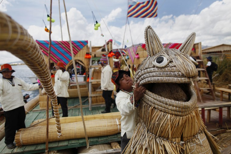 An Andean man prepares a totora raft at the shores of a Uros island at Lake Titicaca before a re-enactment of the legend of Manco Capac and Mama Ocllo in Puno on November 5, 2014. According to an Inca legend, Manco Capac and Mama Occllo emerged from the waters of the lake carrying a golden staff instructed by the sun god Inti to create a temple in the spot where the staff sank into the earth. (REUTERS/Enrique Castro-Mendivil)