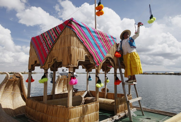An Andean woman decorates a totora raft at the shores of a Uros island at Lake Titicaca before a re-enactment of the legend of Manco Capac and Mama Ocllo in Puno on November 5, 2014. According to an Inca legend, Manco Capac and Mama Occllo emerged from the waters of the lake carrying a golden staff instructed by the sun god Inti to create a temple in the spot where the staff sank into the earth. (REUTERS/Enrique Castro-Mendivil)