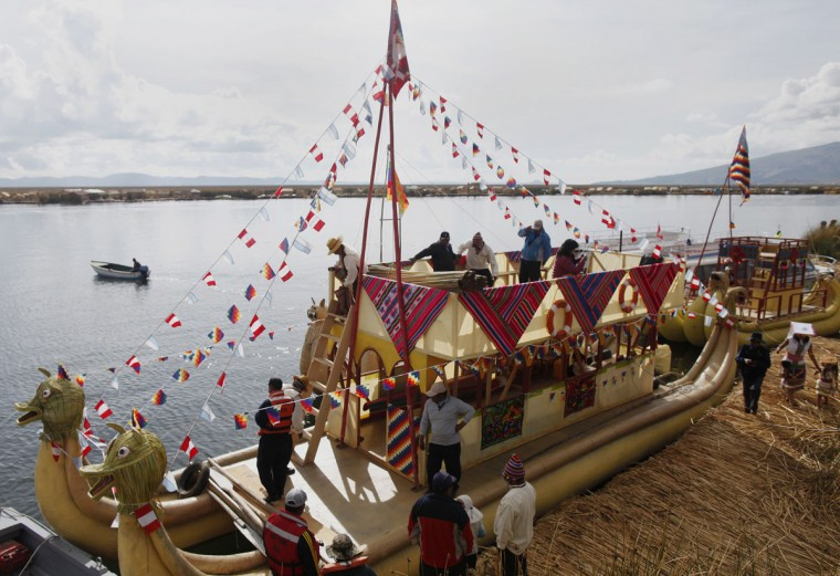 Andeans prepare a totora raft at the shores of a Uros island at Lake Titicaca before a re-enactment of the legend of Manco Capac and Mama Ocllo in Puno on November 5, 2014. (REUTERS/Enrique Castro-Mendivil)