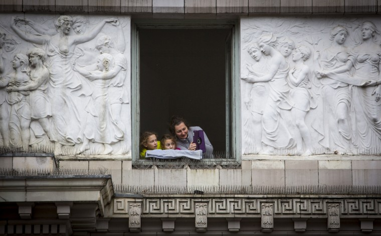 People watch on from a window during the 88th Annual Macy's Thanksgiving Day Parade in New York. (REUTERS/Andrew Kelly)
