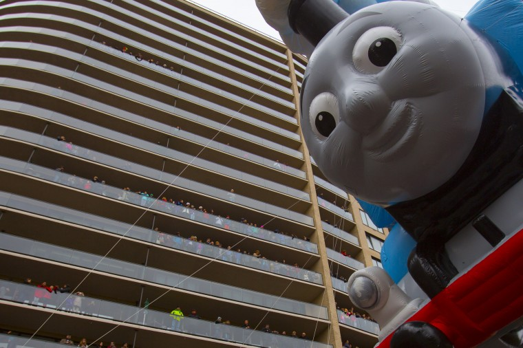 The Thomas the Tank Engine balloon floats by people on balconies during the 88th Annual Macy's Thanksgiving Day Parade in New York. (REUTERS/Andrew Kelly)