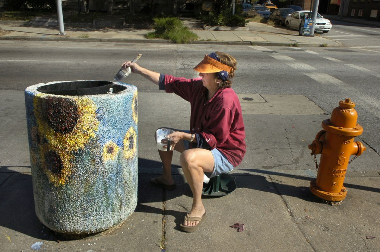 "10/20/08: Anne Blumenberg of Waverly, a retired public interest lawyer and sometime artist puts a coat of polyurethane over her sunflower painting at St. Paul and 29th Sts. She said it was the seventh trash can she has done for the Charles Village Benefits District and has six more cans to go. She's especially proud of her wysteria painting north of 25th St. ""It's nice to give people a smile when they walk down the street,"" she said. (Jed Kirschbaum/Baltimore Sun)"