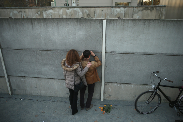 """Visitors peek into the former """"death strip"""" between layers of the former Berlin Wall at the Berlin Wall Memorial at Bernauer Strasse on the day before the 25th anniversary of the fall of the Wall in Berlin, Germany. The city of Berlin is commemorating the 25th anniversary of the fall of the Berlin Wall from November 7-9 with an installation of 6,800 lamps coupled with illuminated balloons along a 15km route where the Wall once ran and divided the city into capitalist West and communist East. The fall of the Wall on November 9, 1989, was among the most powerful symbols of the revolutions that swept through the communist countries of Eastern Europe and heralded the end of the Cold War. Built by the communist authorities of East Germany in 1961, the Wall prevented East Germans from fleeing west and was equipped with guard towers and deadly traps. (Sean Gallup/Getty Images)"""