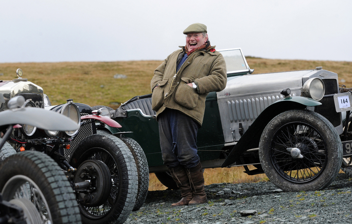 A competitor enjoys the day during a vintage car rally stage at the Honister Slate Mine in the Lake District, England. The event, part of the Lakeland Trials, is held annually by the Vintage Sports Car Club and challenges drivers and their machines through hairpin bends and rocky terrain against a backdrop of awe-inspiring scenery. (Anna Gowthorpe/Getty Images)