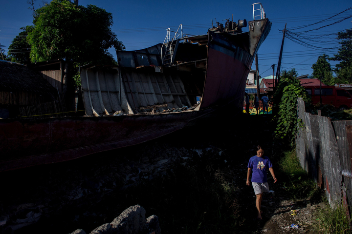 A resident walks past a grounded ship in the Anibong district in Tacloban, Leyte, Philippines. Residents and typhoon survivors from across the central Philippines attended memorial services and visited mass graves honouring those who lost their lives one year ago when Typhoon Haiyan, the strongest typhoon ever to make landfall swept across the region, leaving more than 6000 dead and many more homeless. (Chris McGrath/Getty Images)