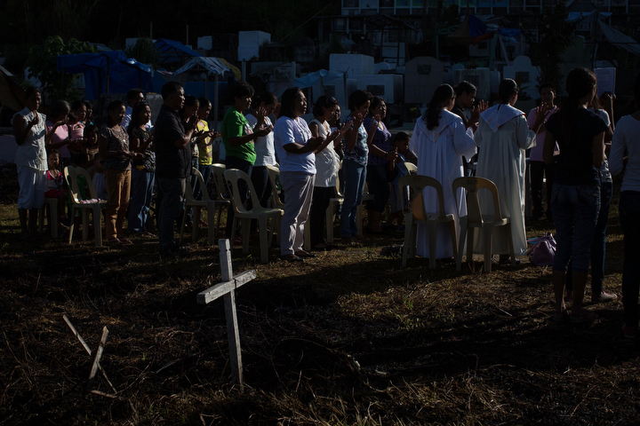 Friends and relatives of typhoon victims participate in a mass at Basper Cemetary, the original site of a mass grave which has now been moved to the Holy Cross Memorial Garden in Tacloban, Leyte, Philippines. Residents and typhoon survivors from across the central Philippines attended memorial services and visited mass graves honouring those who lost their lives one year ago when Typhoon Haiyan, the strongest typhoon ever to make landfall swept across the region, leaving more than 6000 dead and many more homeless. (Chris McGrath/Getty Images)