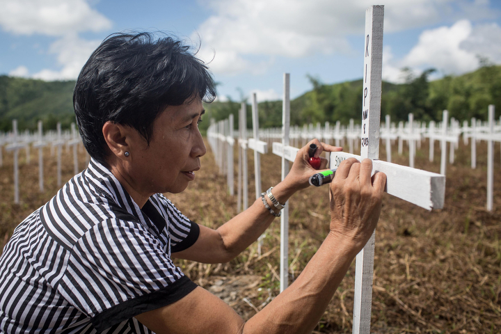 Lutze Mendiou writes the name of her mother and sister onto crosses at the mass grave on the grounds of the Holy Cross Memorial Garden in Tacloban, Leyte, Philippines. Residents and typhoon survivors from across the central Philippines attended memorial services and visited mass graves honouring those who lost their lives one year ago when Typhoon Haiyan, the strongest typhoon ever to make landfall swept across the region, leaving more than 6000 dead and many more homeless. (Chris McGrath/Getty Images)