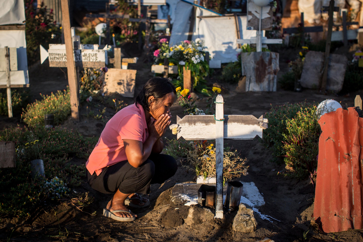 A woman sits at the grave of a loved one at the mass grave site at San Joaquin church on in Tacloban, Leyte, Philippines. Residents and typhoon survivors from across the central Philippines attended memorial services and visited mass graves honouring those who lost their lives one year ago when Typhoon Haiyan, the strongest typhoon ever to make landfall swept across the region, leaving more than 6000 dead and many more homeless. (Chris McGrath/Getty Images)