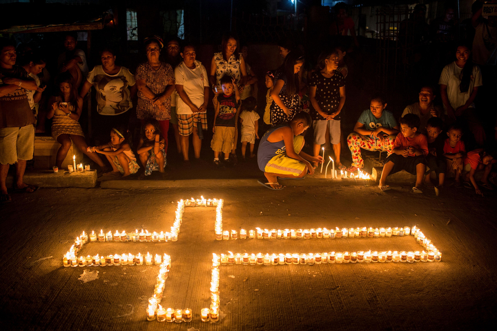 People gather on the street around candles shaped in a cross during the candlelight memorial in Tacloban, Leyte, Philippines. People lined the roads with candles all across Tacloban from the airport to downtown in remembrance of the victims of Typhoon Haiyan. Residents and typhoon survivors from across the central Philippines attended memorial services, candlelight vigils and visited mass graves honouring those who lost their lives one year ago when Typhoon Haiyan, the strongest typhoon ever to make landfall swept across the region, leaving more than 6000 dead and many more homeless.(Chris McGrath/Getty Images)